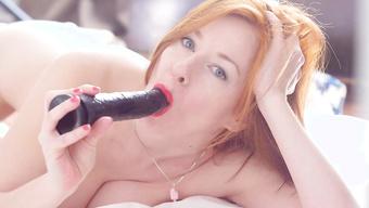 Рыжая шалунья мастурбирует вагину большим дилдо в спальне